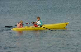 Two youths, ages 12 and 6, row a TurboII at Longboat key on the gulf of Mexico off the Florida Coast